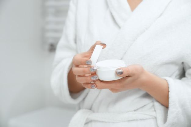 Молодая женщина, держащая крем для тела или лица в ванной комнате