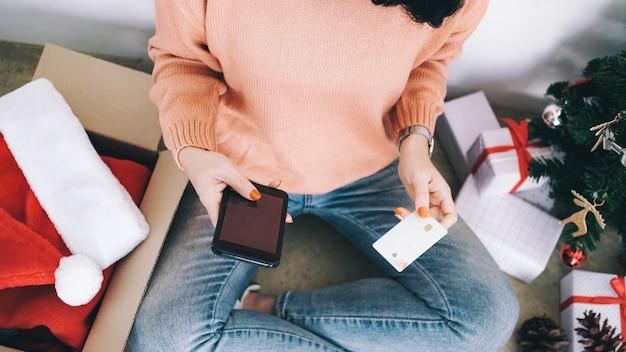Молодая женщина держа кредитную карточку и делая покупки онлайн.