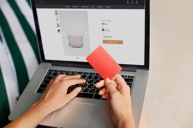 クレジットカードを保持しているとラップトップに入力してオンラインショッピングホームコンセプトの若い女性。インターネットバンキング、お金を使う
