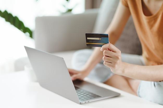 Молодая женщина, держащая кредитную карту и использующая портативный компьютер. интернет-магазины, интернет-банкинг, электронная коммерция, трата денег, работа из дома.