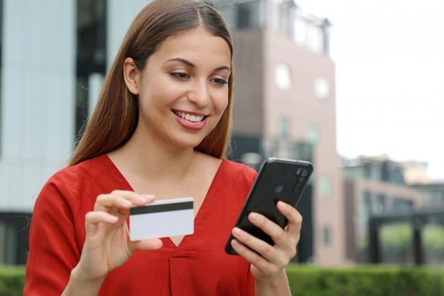クレジットカードを保持し、スマートフォンを使用して若い女性。オンラインショッピング、eコマース、インターネットバンキング、お金を使う、スマートフォンアプリで作業する。