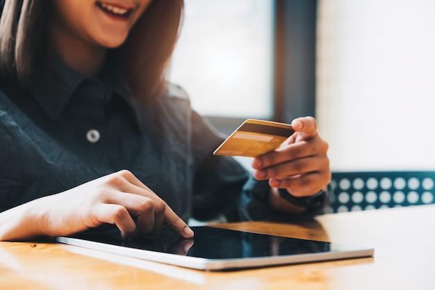 신용 카드를 들고 태블릿 컴퓨터를 사용 하여 젊은 여자. 온라인 쇼핑 개념.