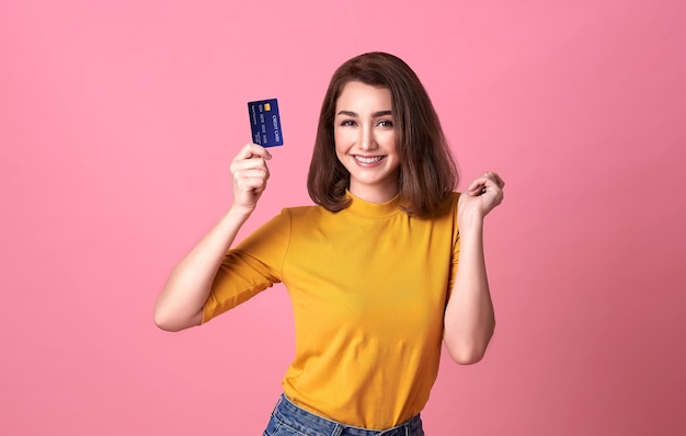 Young woman holding credit card  in casual yellow shrit with gorgeous in trust and confidence for money transaction isolated on bright pink wall.