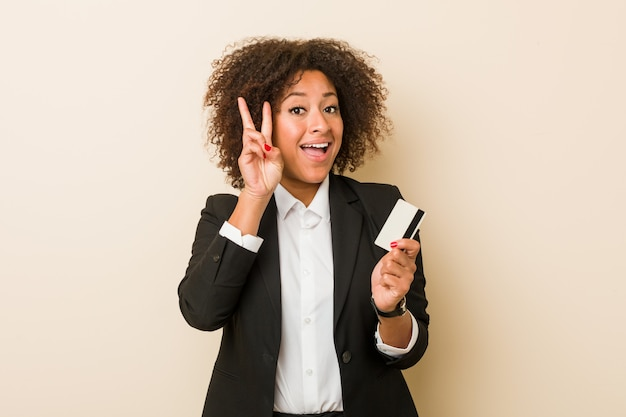 Young woman holding a credit card showing victory sign and smiling broadly.