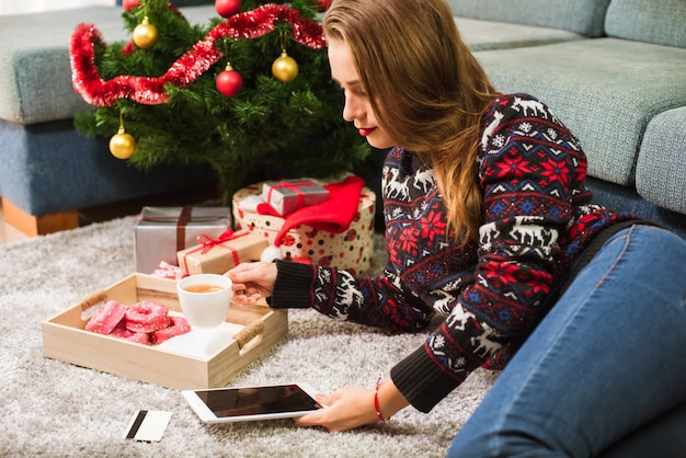 Young woman holding credit card and tablet on christmas
