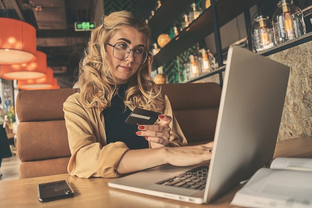 Young woman holding credit card and using laptop
