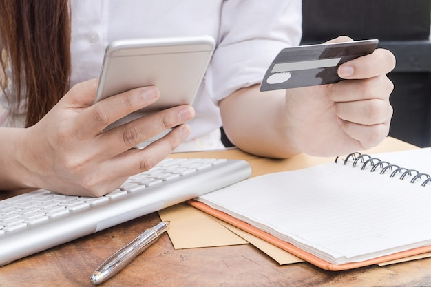 Young woman holding credit card and using mobile phone. online shopping concept