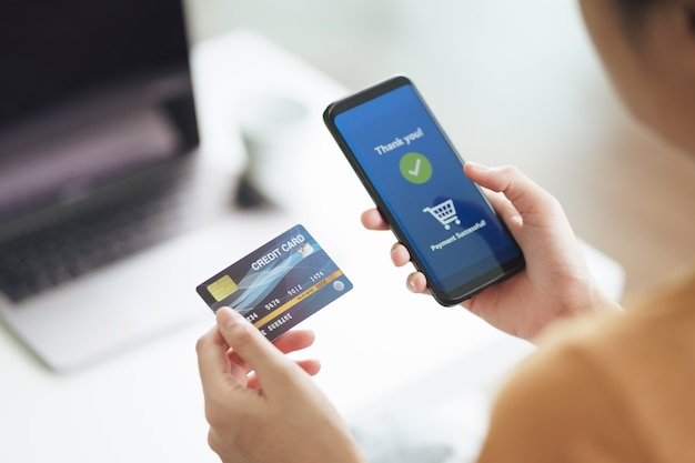 Young woman holding credit card and using smart phone for online shopping, internet banking, e-commerce, spending money, working from home concept.
