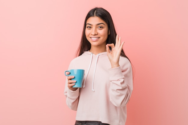 Young woman holding a cup cheerful and confident and showing ok gesture