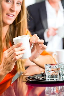 Young woman holding cup of coffee in hand