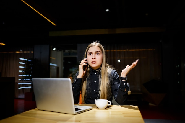 Young woman holding a cup of coffee and using laptop computer talking on the phone. businesswoman working from home. work from home