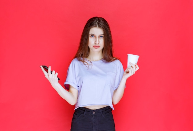 Giovane donna che tiene una tazza di bevanda e uno smartphone nero con una faccia delusa.