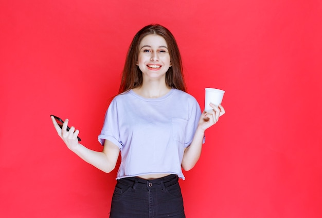 Young woman holding a cup of drink and a black smartphone with smiling face.