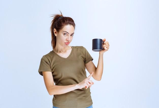 Giovane donna che tiene una tazza di bevanda e la indica