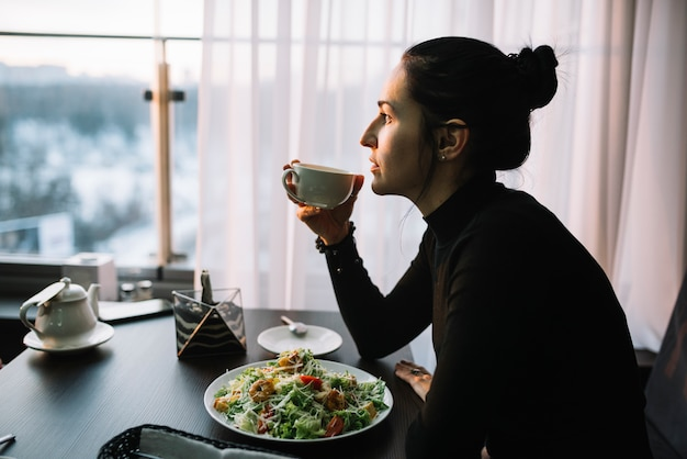 Young woman holding cup of drink at table with salad near window
