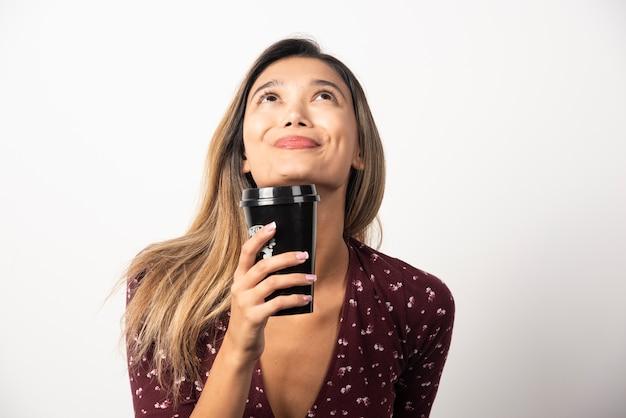Giovane donna con una tazza di bevanda sul muro bianco.