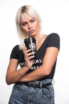 真剣な表情で白い壁にコーヒーを保持している若い女性。