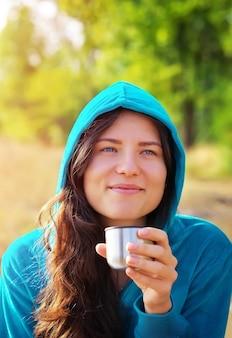一杯のコーヒーやお茶を持って笑っている若い女性。公園でテイクアウトのコーヒーを飲む美しい若いブロンドの女性。一杯のコーヒーと屋外のかわいい女の子