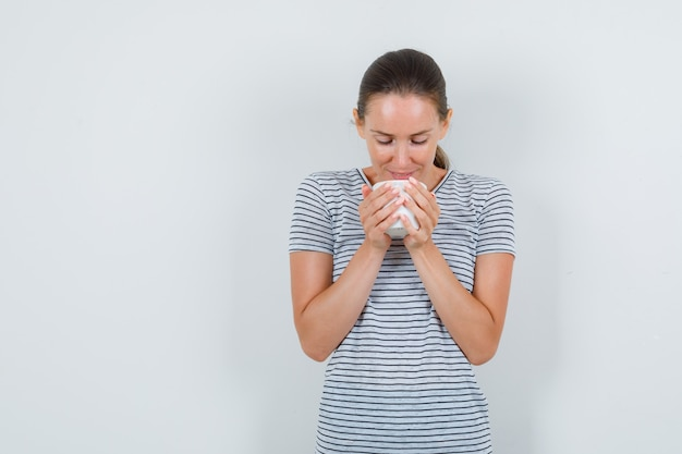 お茶を持って、tシャツの正面図で笑っている若い女性。