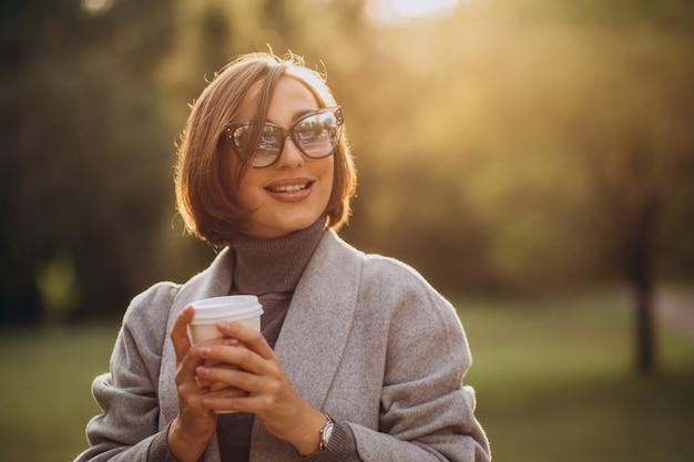 公園で暖かいコーヒーのカップを保持している若い女性