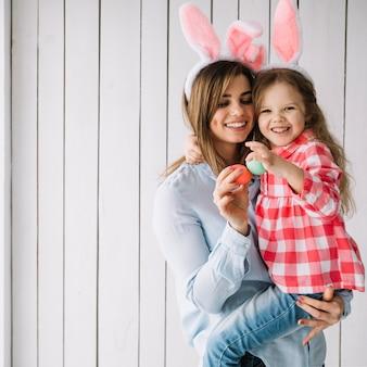 Молодая женщина держит дочь на руках с пасхальными яйцами