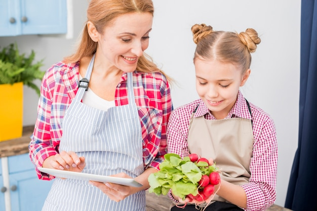 Young woman holding digital tablet in hand looking at her daughter holding radish