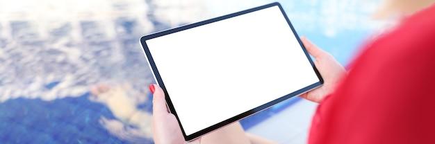 Молодая женщина, держащая цифровой планшет с пустым экраном у бассейна
