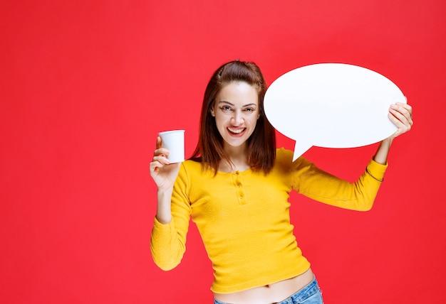 Giovane donna con in mano una tazza di bevanda usa e getta e un pannello informativo ovale