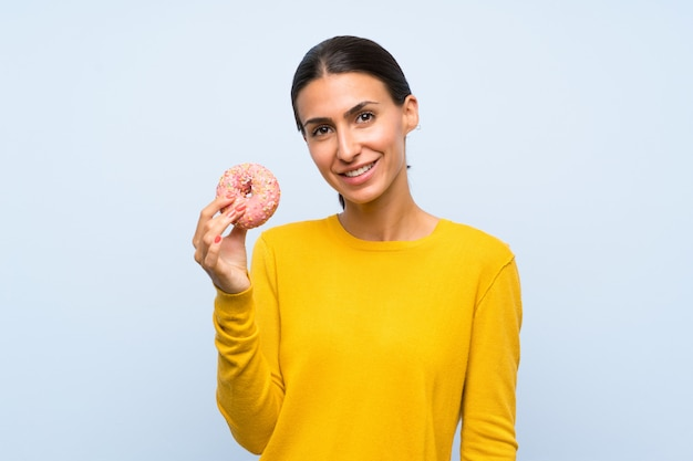 Young woman holding a donut over isolated blue wall smiling a lot