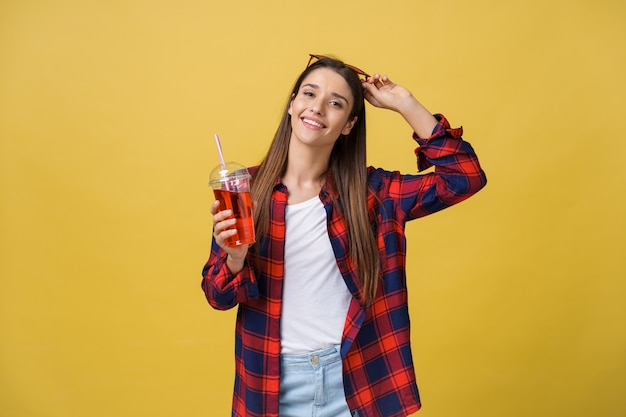 Young woman holding and drinking cold drink beverage in casual clothes. pretty girl smiling happy laughing looking at camera.