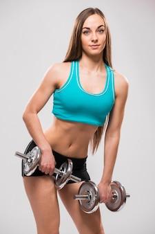 Giovane donna che tiene un dummbell su sfondo grigio