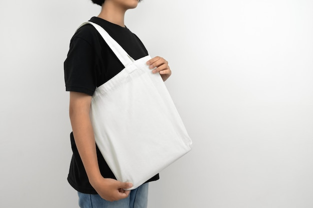 Young woman holding eco cotton bag isolate on white
