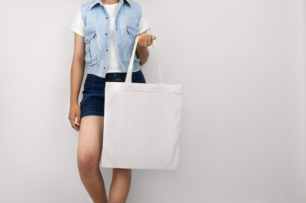 Young woman holding eco cotton bag on wall white
