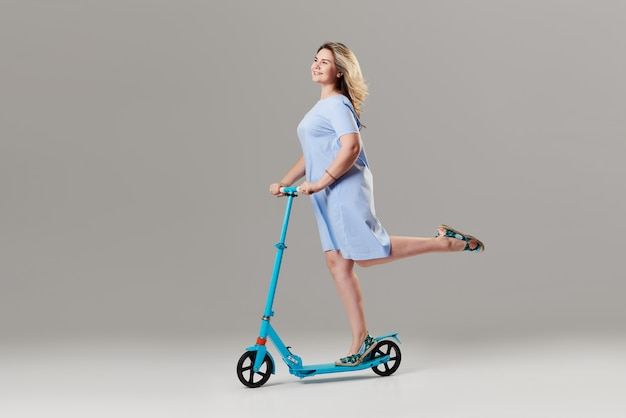 Young woman holding the electric scooter and riding it while feeling delighted. full length portrait of an overjoyed girl riding a scooter on white wall