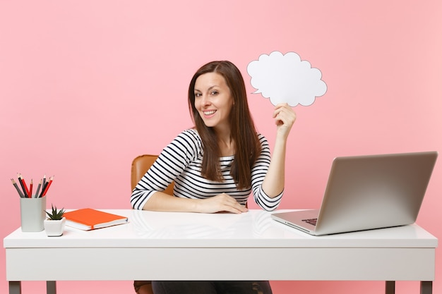 Young woman holding empty blank say cloud speech bubble sit and work at white desk with pc laptop isolated on pastel pink background. achievement business career concept. copy space for advertisement.