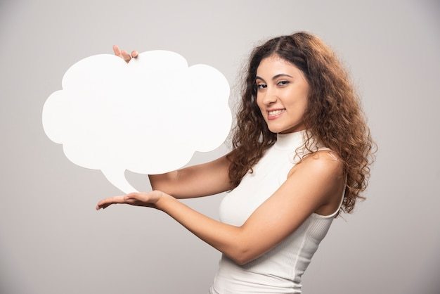 Young woman holding empty blank white speech bubble. high quality photo