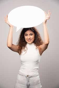 Giovane donna che tiene il fumetto bianco vuoto vuoto sovraccarico. foto di alta qualità