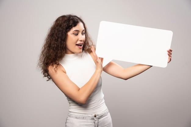 빈 빈 흰색 연설 포스터를 들고 젊은 여자. 고품질 사진