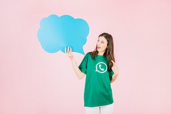 Young woman holding empty blue speech bubble over pink background