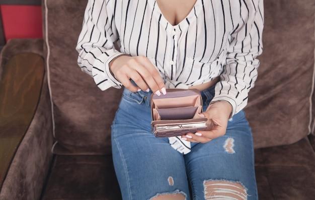 Молодая женщина, держащая пустой коричневый бумажник дома.
