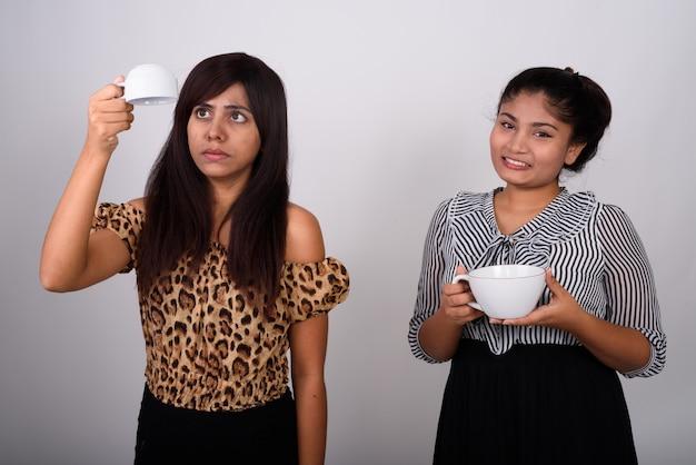 젊은 행복 한 십 대 소녀 커피 컵을 들고 거꾸로 빈 커피 컵을 들고 젊은 여자