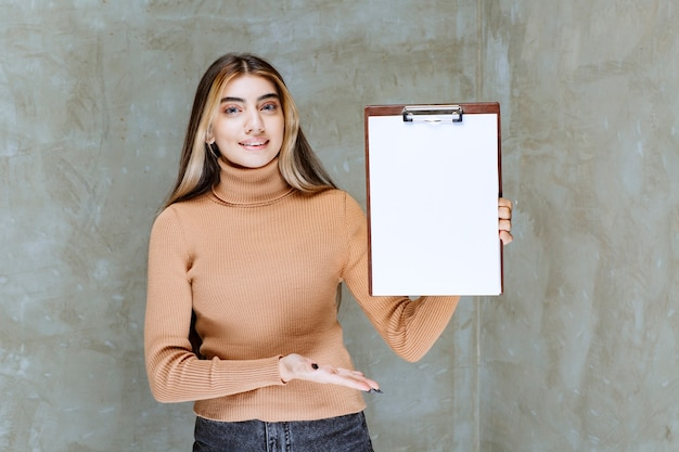 Young woman holding an empty notepad on a stone