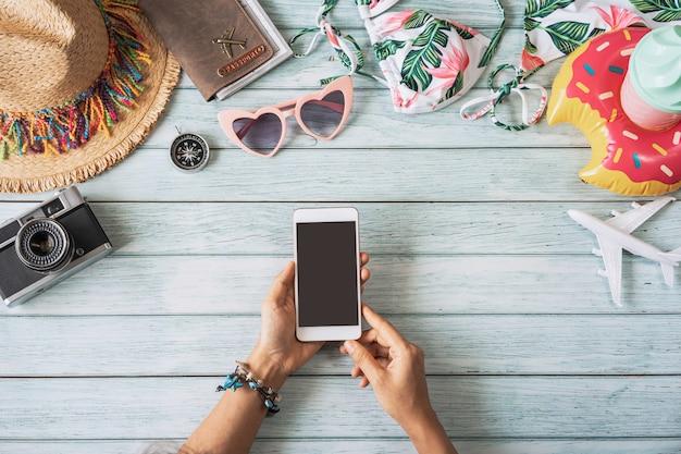 Молодая женщина, держащая смартфон пустой экран с путешествия летние аксессуары и предметы на деревянном столе, концепция планирования путешествий