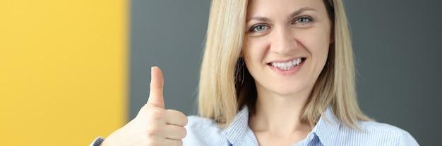 Молодая женщина держит учебник английского языка и показывает большой палец вверх, изучая концепцию иностранных языков