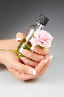 Молодая женщина держит бутылку эфирного масла и цветок