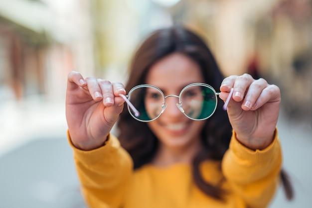 Young woman holding eyeglasses toward camera outdoors.