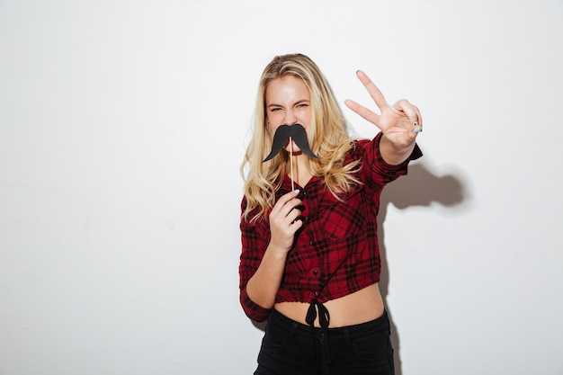 Young woman holding fake moustache showing peace gesture.