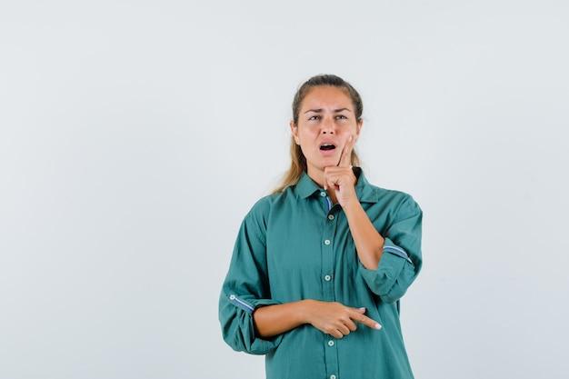 Молодая женщина, держащая палец на щеке, думает в синей рубашке и выглядит озадаченным