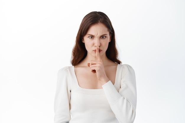 입술 입에 손가락을 대고 있는 젊은 여성, 카피 공간이 있는 흰색 빈 스튜디오 벽에 고립되어 서 있는 젊은 여성, 침묵 속에서 쉿 제스처의 비밀을 보여주는 밀레니얼 가십 걸