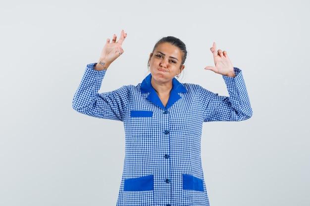 Giovane donna che tiene le dita incrociate, guance gonfie in camicia pigiama a quadretti blu e sembra carina. vista frontale.